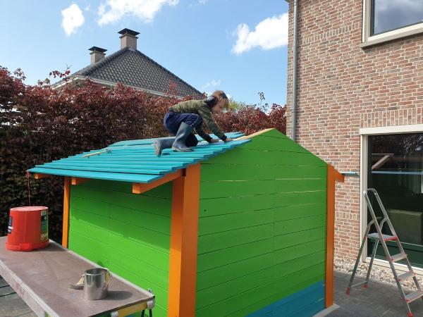 De geschilderde planken worden op het dak getimmerd